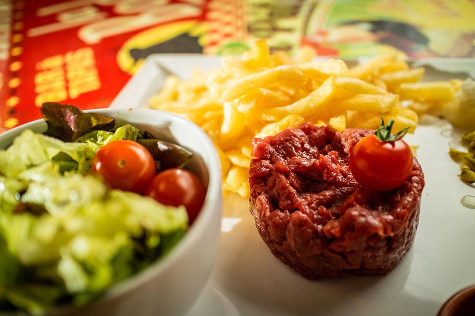 Tartare de Boeuf au Couteau «180 g, boeuf Charolais cru coupé au couteau, jaune d'oeuf, oignon, persil, câpres, cornichon, non préparé servi avec frites maison et salade»