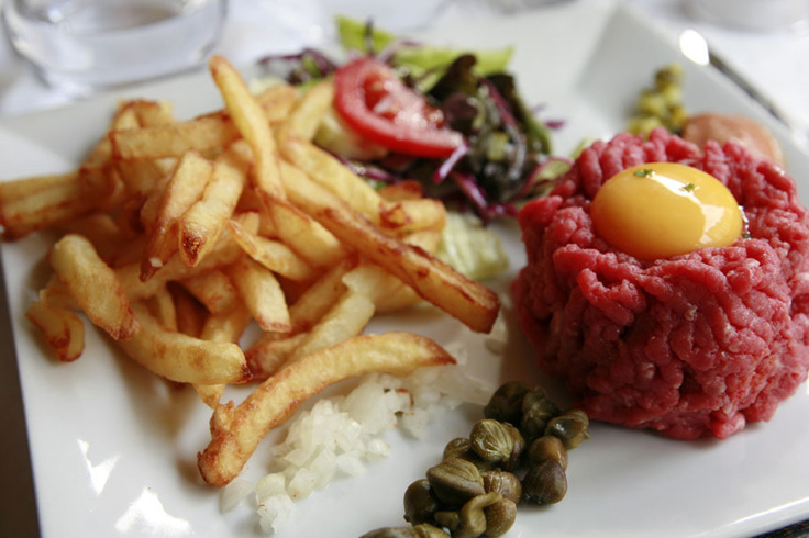 Handcut beef tartar  180gr «raw Charolais chopped in with a knife, egg yolk, onion, parsley, capers, gherkin, not prepared served with homemade french fries and salad»